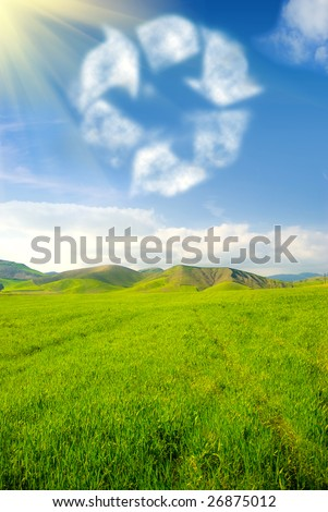 Recycle symbol in the sky with grassland landscape - stock photo