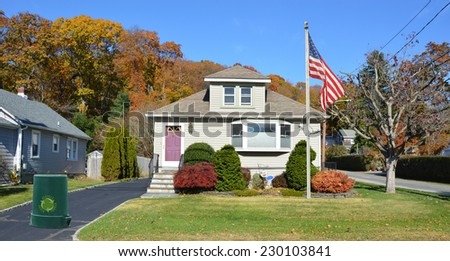 Recycle Trash Can American Flag pole on front yard lawn of suburban bungalow style home residential neighborhood clear blue sky USA - stock photo