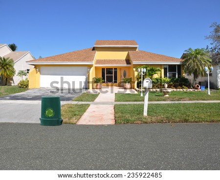 Recycle trash container at driveway's end of suburban ranch home residential neighborhood sunny blue sky USA