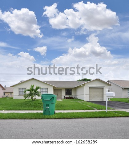 Recycle Trash Container Front Yard Lawn Suburban Ranch Style Home Residential Neighborhood Blue Sky Clouds USA - stock photo