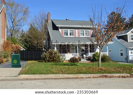 Recycle trash container suburban bungalow style home autumn day residential neighborhood blue sky USA - stock photo
