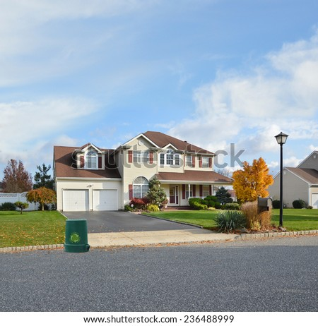 Recycle trash container suburban Mcmansion home autumn day residential neighborhood USA blue sky clouds