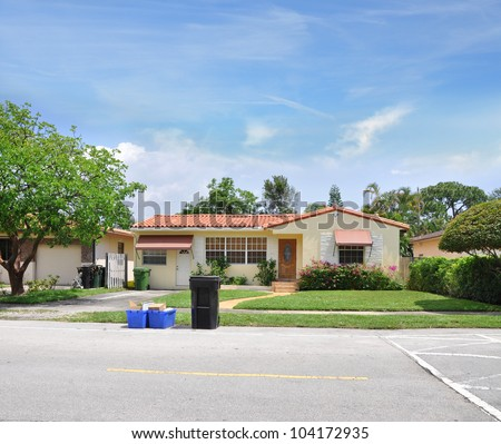 Recycle Trash Garbage Containers Curbside Suburban Ranch Home in Residential Neighborhood Sunny Blue Sky Day - stock photo