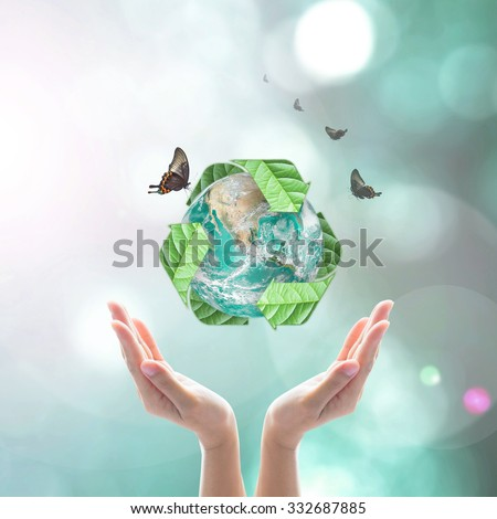 Recycled arrow sign leaf around eco green globe over beautiful women human hand on blurred abstract bokeh greenery background: Recycle reduce reuse CSR concept: Element of the image furnished by NASA  - stock photo