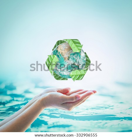 Recycled arrow sign leaf around green globe on beautiful woman human hands on blurred abstract natural turquoise blue water background: CSR eco bio concept: Element of this image furnished by NASA    - stock photo
