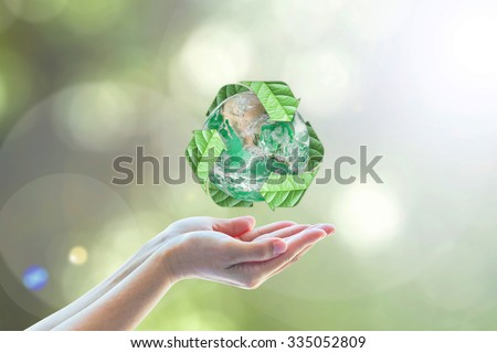 Recycled arrow sign leaf around green globe over beautiful woman human hand on blurred abstract bokeh greenery background: Recycle, reduce, reuse concept: Elements of this image furnished by NASA   - stock photo