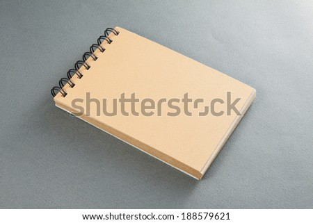 recycled paper notebook front cover, gray background - stock photo