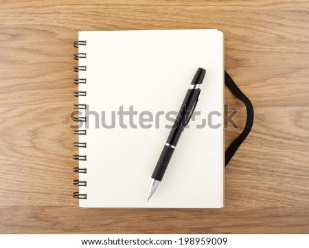 Recycled paper notebook with black elastic band and pen on a table  - stock photo