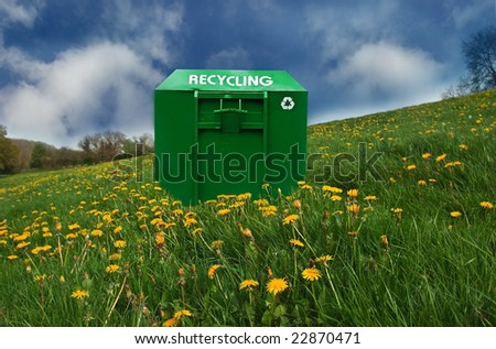 Recycling bin in a dandelion covered meadow. - stock photo