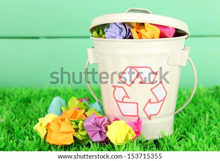 Recycling bin on green grass on color wooden background - stock photo