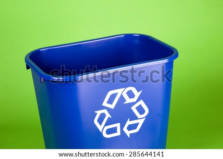 Recycling bin set against a green background.  Great conceptual message and room for your own text. - stock photo