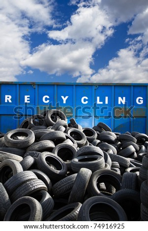 Recycling container and car tires, landfill over blue cloudy sky - stock photo