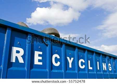 Recycling container over blue sky and car tire, ecology and environment concept