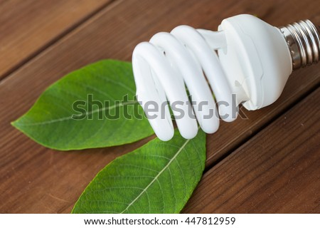 recycling, electricity, environment and ecology concept - close up of energy saving lighting bulb on wooden boards and green leaf - stock photo