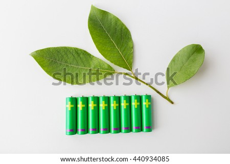 recycling, energy, power, environment and ecology concept - close up of green alkaline batteries and leaf - stock photo