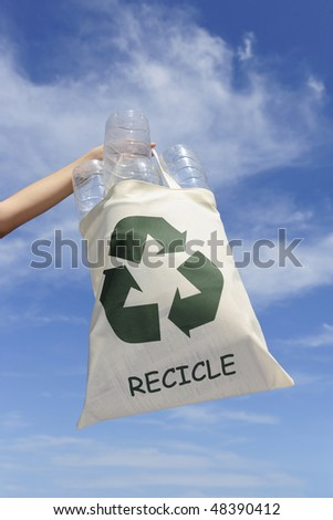 recycling: hand holding bag with plastic bottles against blue sky - stock photo