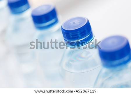 recycling, healthy eating, industry, packing and food storage concept - close up of plastic bottles with pure drinking water