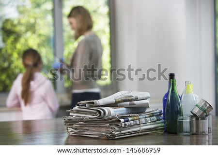 Recycling material on kitchen table with family in background - stock photo