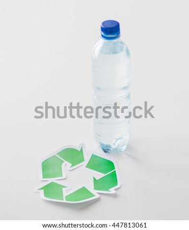 recycling, reuse, garbage disposal, environment and ecology concept - close up of plastic water bottle with green recycle symbol on table - stock photo