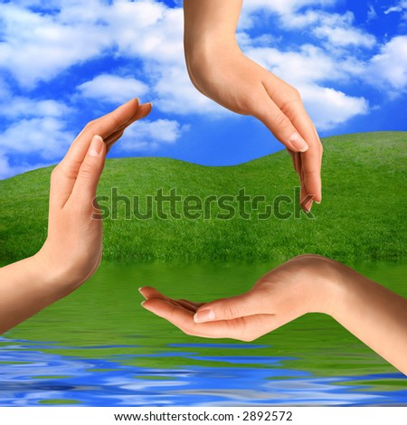 Recycling symbol made from hands on summer nature background Environment and ecology artistic concept - stock photo