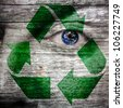 Recycling symbol painted on face and earth as eye to create awareness for a green earth - Elements of this image furnished by NASA - stock photo