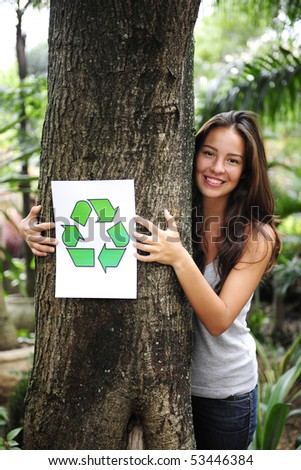 recycling: woman in the forest holding a recycle sign smiling - stock photo