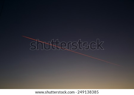 Red airplane vapor trail in the morning sky