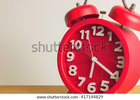 Red alarm clock close up on wooden table. Emphasizing copy space on left side. - stock photo