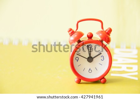 Red alarm clock put on diary book. - stock photo