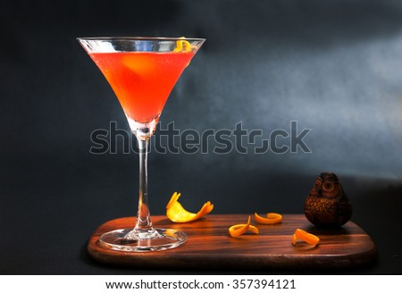 red alcohol cosmopolitan cocktail decorated with citrus lemon in martini cocktails glass on wooden cutting board isolated on a black background - stock photo