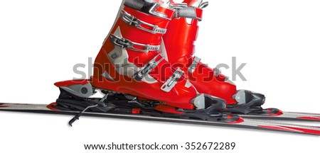 Red alpine ski boots with four buckles in ski binding. One shoe is completely fastened to the ski, a second just put in binding.