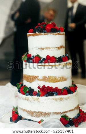Red and black berries decorate white wedding cake
