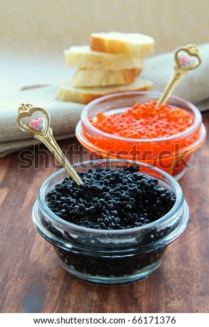 red and black caviar in glass jars with gold spoons - stock photo