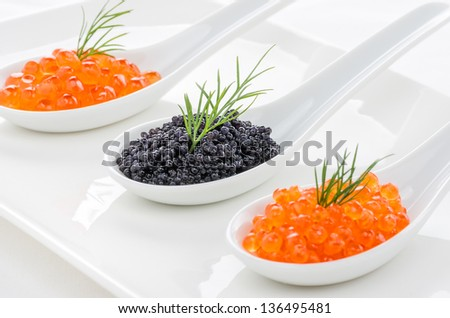 Red and black caviar on porcelain spoons - stock photo