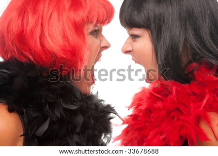 Red and Black Haired Women with Boas Screaming at Each Other on a White Background. - stock photo