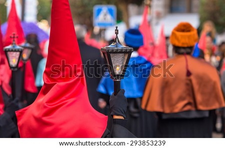 Red and black Nazareno holding a candle during Holy Week in Valladolid. - stock photo