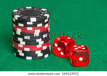 red and black poker chips and red dice on a green casino felt