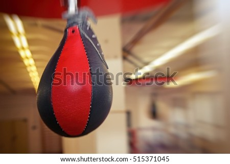 Red and black punching bag with gym background