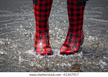 Red and black rubber boots splashing in a puddle after rainfall. - stock photo