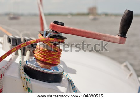 Red and black winch handle inserted into large winch with red and yellow line wrapped - stock photo