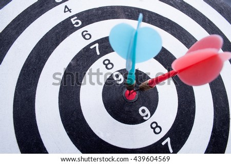 Red and blue dart arrows hitting in the target center of dartboard - stock photo