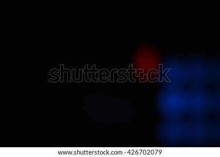 Red and blue defocused blurry circular lights glowing soft in the darkness. They soothe, brings a positive and located at the bottom right of the photo. - stock photo