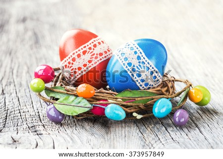 Red and blue Easter eggs decorated with lace in small decorative nest. Selective focus - stock photo