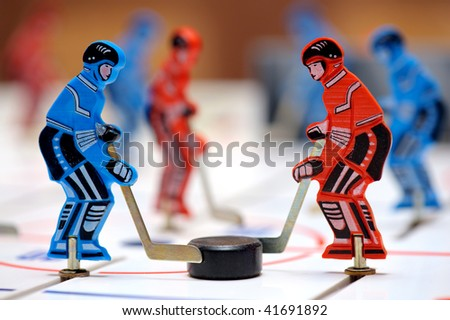Red and blue figures of hockey players of children's board game - stock photo