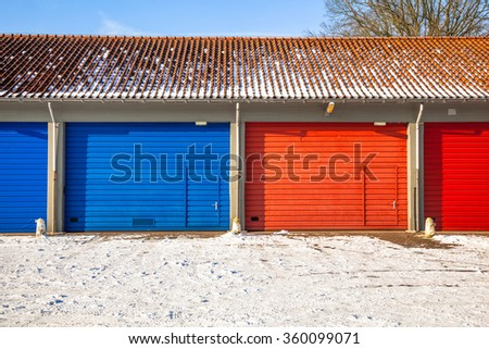 Red and Blue Fire Brigade Garage Doors and Frost roads service next to each other on a Snowy Winter Day