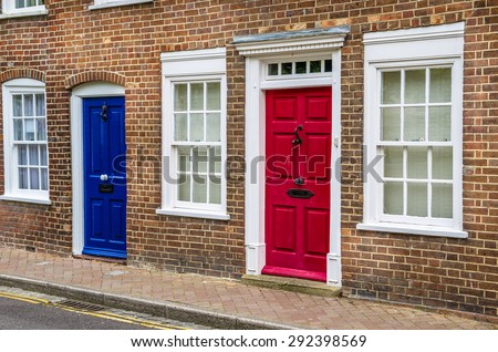 Red and Blue Front Doors and White Windows on a Terraced House in UK. Traditional British Doors. - stock photo