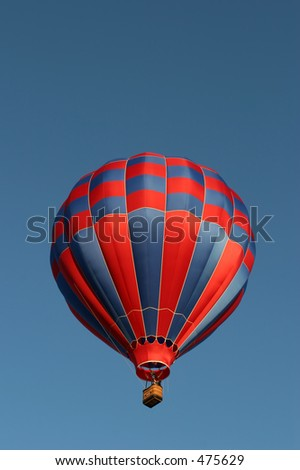 red and blue hot air balloon against a clear blue sky