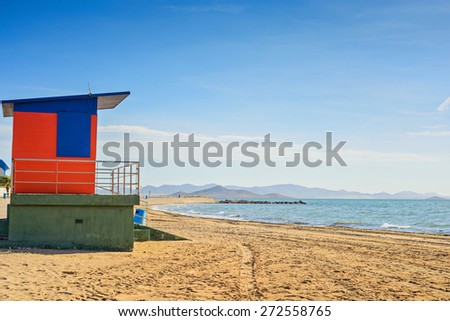 Red and blue lifeguard house on the sandy beach - stock photo