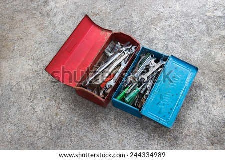 Red and blue metal tool box with many tools on concrete floor - stock photo