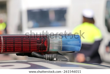 Red and blue siren police car during the roadblock with policemen in uniform - stock photo